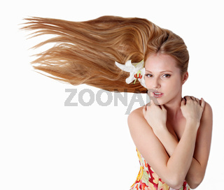 Beautiful blond girl with lily flower in studio