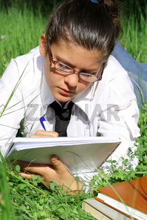student writing or studying outdoors on campus