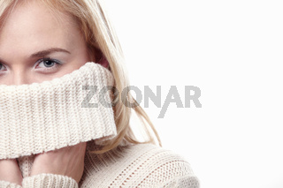 Attractive girl covers her face with a sweater on a white background