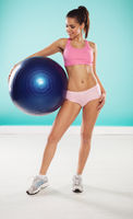 Woman posing with a pilates ball