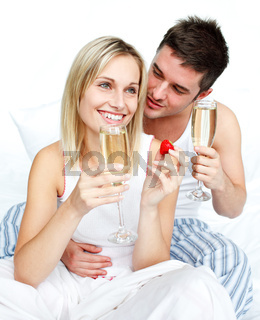 Young lovers eating strawberries and drinking champagne