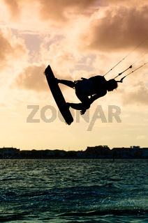 Silhouette of a kitesurfer flying