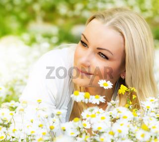 Happy girl enjoying daisy flower field