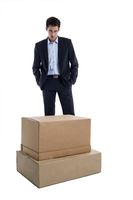 Pensive businessman in front of a box