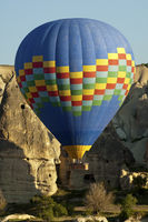 Hot air balloon manoeuvres between tuff rock cones