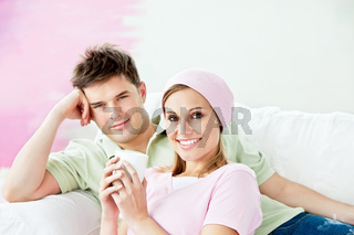Relaxing couple lying on a sofa after painting a room