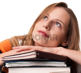 Young girl student with pile of books dreaming