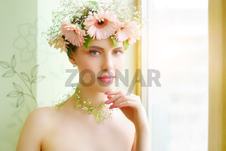 beautiful girl wearing wreath of flowers on light background