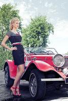 Elegant girl poses near the red car. Cabriolet jag