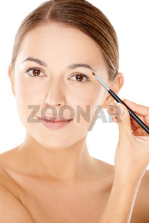 Woman holding a tiny cosmetic brush