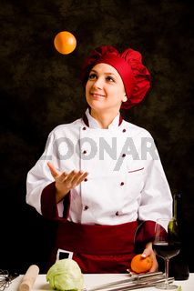 Chef juggling with orange