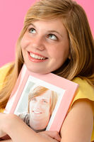 Teenage girl embracing picture of her boyfriend