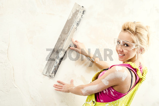 Female with putty knife working indoors