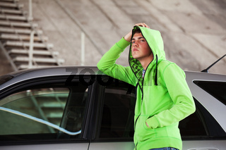 Young man standing against a car