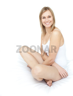 Delighted smiling woman sitting on a bed against a white background