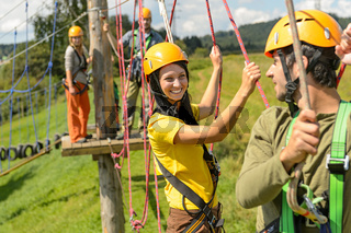 Young couple in safety equipment adventure park