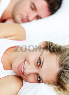 Beautiful smiling woman in bed with her boyfriend