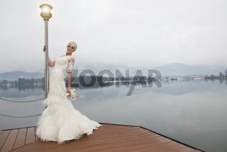 Junge blonde Braut stehend am See