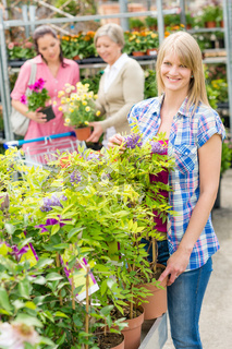 Smiling woman at garden center shopping plants