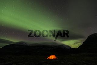 Nordlicht (Aurora borealis) ueber einem Zelt mit Blick auf den Berg Sinnitjohkka, Kebnekaisefjaell, Lappland