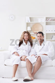 Attractive happy couple in robes at home