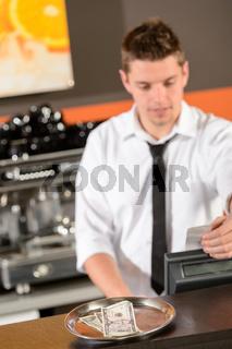 Young bartender in uniform taking cash dollar