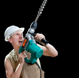 The builder in a protective helmet holds the professional puncher-hammer with a drill of the big diameter