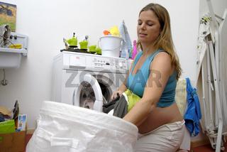 Schwangere Frau sortiert Wäsche