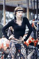 Beautiful girl on carousel amusement ride at the p
