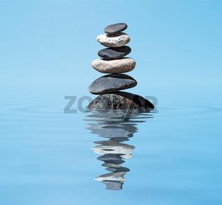 Zen balanced stones stack in lake  balance peace silence concept