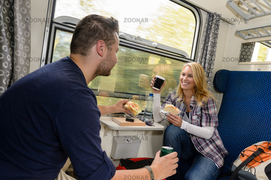 Couple enjoying sandwiches traveling with train