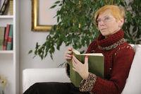 Seniorin liest ein Buch zuhause