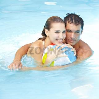 Paar mit Wasserball im Pool