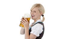 Hübsches blondes Mädchen im Dirndl trinkt aus Oktoberfest Mass Bier