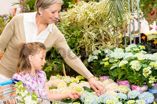 Garden center girl with grandmother buy flowers