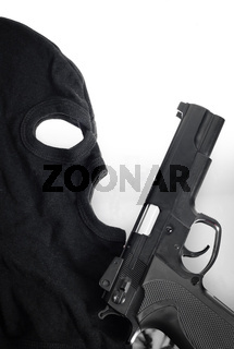 Pistol and mask of a thief over white
