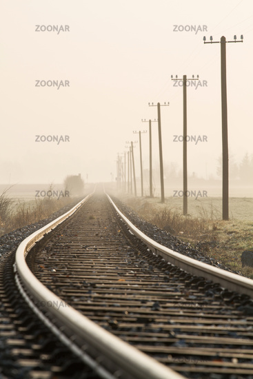 Single-track railway line in the morning fog