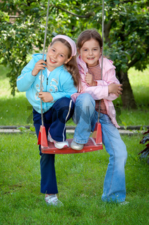 Two young girls on the garden swing