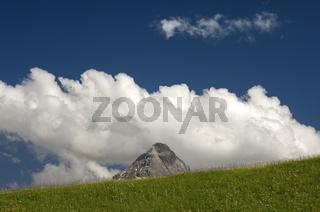 Die Gipfelpyramide der Ehrwalder Sonnenspitze erhebt sich hinter einem grünen Hügel in weissen Kumuluswolken