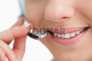 Close-up on a smiling businesswoman mouth speaking in headset