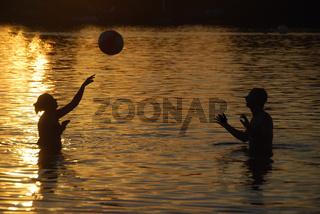 paar spielt ball im wasser
