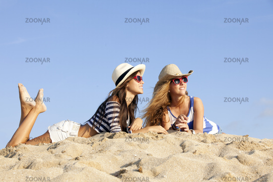girls laying in sand on summer vacation
