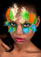 Black women with colored feathers in face.