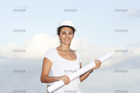 Engineer with a drawing in hand against blue sky