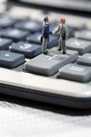 Miniature men shaking hands on a calculator