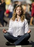 Gelassenheit und Ruhe im Alltag: Frau meditiert auf Straße
