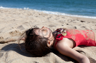 Close up of a Little Girl Relaxing on the Beach Covered in Sand
