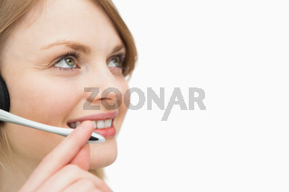 Woman with headset smiling while looking up