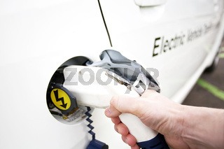 Hand is holding Electric Car Charging nozzle