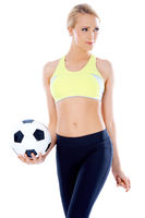 Female soccer player posing with ball
